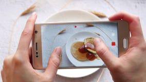 Händer för kvinna` s, frukostskott vid telefonen Flickan tar bilder av mat Närbild