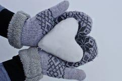 Händer för kvinna` s i hemtrevliga varma tumvanten håller hjärtan ut ur snön mot bakgrunden av snö Royaltyfria Foton