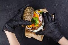 Händer för kvinna` s i svarta rubber handskar är den hållande saftiga svarta bullehamburgaren Royaltyfria Bilder