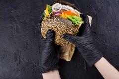 Händer för kvinna` s i svarta rubber handskar är den hållande saftiga svarta bullehamburgaren Arkivbild
