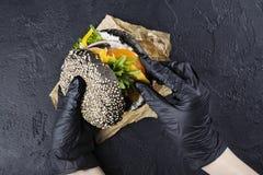 Händer för kvinna` s i svarta rubber handskar är den hållande saftiga svarta bullehamburgaren Arkivfoton