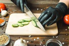 Händer för kvinna` s klippte en gurka, nästan tomaterna, paprikan och vitlöken Fotografering för Bildbyråer