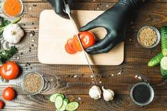 Händer för kvinna` s klippte en tomat, bredvid lögn paprikan, örter, gurkor och smaktillsatser arkivfoton
