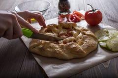 Händer för kvinna` s klippte pajen för den nya grönsaken med zucchinin, tomater och ost Royaltyfri Foto