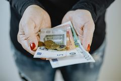 Händer för kvinna` s med eurosedlar och en plånbok Royaltyfria Foton