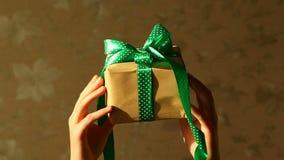Händer för kvinna` s med gåvaasken med det gröna bandet, feriebegrepp
