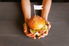 Händer för kvinna` s med hamburgaren arkivfoto