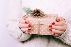 Händer för kvinna` s med julgåvaasken arkivfoto