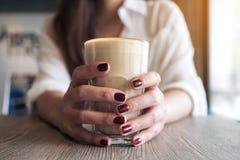 Händer för kvinna` s med rött spikar färg som rymmer ett exponeringsglas av kaffe Royaltyfria Foton