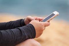Händer för kvinna` s med Smartphone att smsa royaltyfria foton