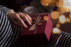 Händer för kvinna` s rymmer en gåva slitage vit vinter för härlig stående för begreppsklänningflicka Arkivfoton