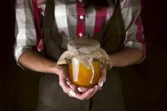 Händer för kvinna` s rymmer en krus av honung Arkivfoto