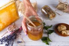Händer för kvinna` s rymmer en krus av honung Arkivbild