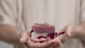Händer för kvinna` s rymmer en stång av rosa tvål Closeupen är fudgy; medan hon flyttar henne händer framåtriktat, får det klart stock video
