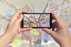 Händer för kvinna` s tar en bild av många godisar på en smartphone Bild av färgrika sötsaker, karamellgodisar och klubbor Royaltyfri Fotografi