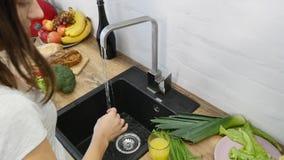 Händer för kvinna` s tvättar nya grönsaker arkivfilmer