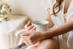 Händer för kvinna` som s rymmer den vitt kopp te eller kaffe på ljus rumbakgrund Morgontid för frukost royaltyfri bild