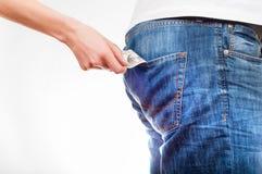 Händer för kvinna` som s tillbaka drar dollarräkningen ut ur jeans po för man` s Arkivbilder