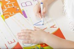 Händer för litet barn som skrivar brev A Royaltyfria Bilder