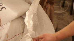 Händer för man` s öppnar en påse av malt reva Mala av malt för att producera öl på bryggeriet arkivfilmer