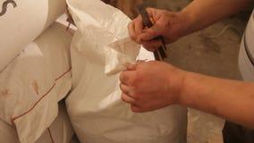 Händer för man` s öppnar en påse av malt reva Mala av malt för att producera öl på bryggeriet lager videofilmer