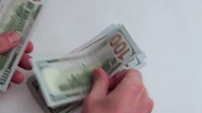Händer för man` s betraktar amerikanska hundra-dollar räkningar i beloppet av tusen dollar Närbild Begrepp vitt lager videofilmer