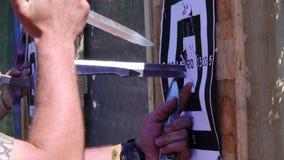 Händer för man` s får en kniv från målet Kasta knivar på målet från ett frilufts- avstånd som flyger knivar, kors arkivfilmer