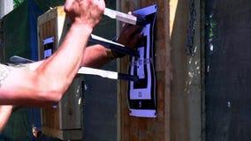 Händer för man` s får en kniv från målet Kasta knivar på målet från ett frilufts- avstånd som flyger knivar, kors stock video