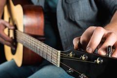 Händer för man` s justerar den akustiska gitarren Royaltyfria Foton