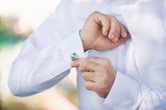 Händer för man` s knäppas upp manschettknappar på en vit skjorta Brudgummen går till bröllopnärbilden Royaltyfria Bilder