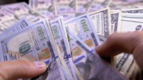 Händer för man` s rymmer en hög av amerikanska dollar mot bakgrunden av roterande pengar stock video