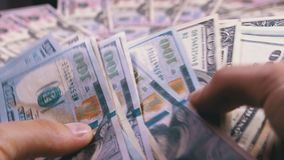 Händer för man` s rymmer en hög av amerikanska dollar mot bakgrunden av roterande pengar arkivfilmer