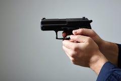 Händer för man` som s siktar med vapnet arkivfoton