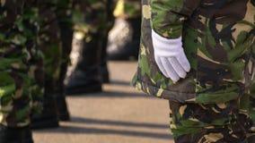 Händer för militär man som sätter på några vita handskar arkivbild