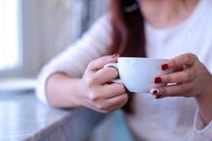 Händer för modell för Closeupskönhetstående med rött mode spikar att måla i den varma tröjan som rymmer en vit kopp kaffe, te, mj arkivbilder