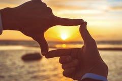 Händer för ` s för man för sammansättningsfingerram fångar spektakulär solnedgång arkivbild