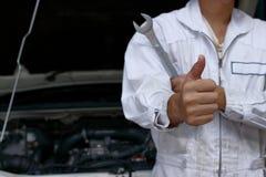 Händer för slut upp av den yrkesmässiga unga mekanikern man upp visningtummen som tecken av framgång med bilen i öppen huv på gar Arkivbild