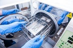 Händer för tandläkareassistent` s får sterilisera ut medicinska instrument från autoclaven Selektivt fokusera Royaltyfria Foton