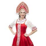 Händer för ung kvinna för leende på höftståenden i traditionell dräkt för ryss -- rött sarafan och kokoshnik Royaltyfria Bilder