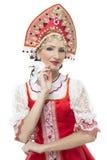 Händer för ung kvinna för leende på höftståenden i traditionell dräkt för ryss -- rött sarafan och kokoshnik Fotografering för Bildbyråer