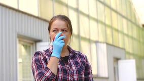 Händer för ung kvinna med handskar som rymmer röda tomater som arbetar i ett växthus arkivfilmer