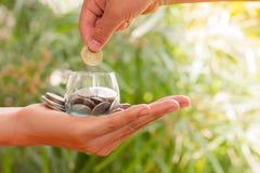 Händer för ung kvinna som rymmer den glass kruset med pengarmynt inom arkivbild