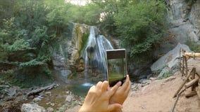 Händer gör ett foto av en vattenfall på telefonen stock video