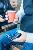 Händer genom att använda en telefon som smsar på smartphonen app och den pappers- koppen kaffe för innehav royaltyfri fotografi