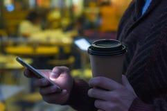 Händer genom att använda en telefon som smsar på smartphonen app och den pappers- koppen kaffe för innehav fotografering för bildbyråer