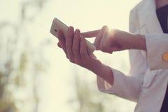 Händer genom att använda smartphonen Arkivfoton