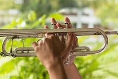 Händer griper trumpeten royaltyfri foto