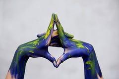 Händer i blå målarfärg med gula brytningar, händer av konstnären och idérik person Yoga f?r h?nder royaltyfri fotografi