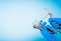 Händer i blåa handskar som rymmer tand- utrustning för kirurgi arkivbilder
