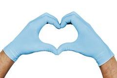 Händer i blåa medicinska handskar som visar hjärtatecknet som isoleras på vit bakgrund arkivfoto